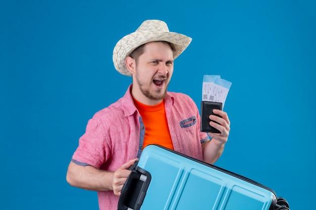 Jonge knappe reizigersmens die in de zomerhoed vliegtuigtickets en koffer houden zeer opgewonden en gelukkig status over blauwe muur