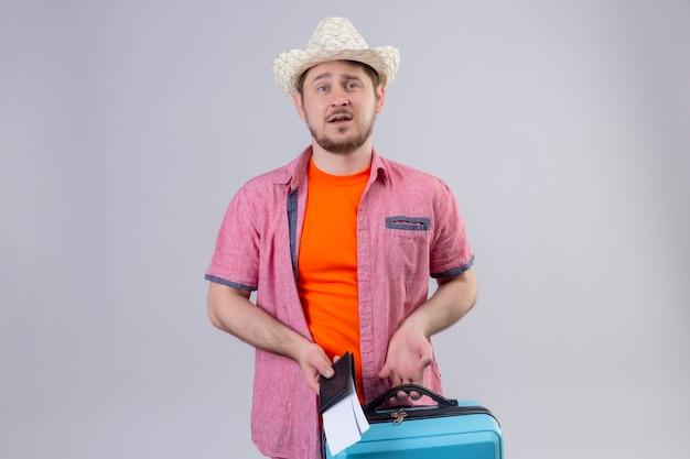 Jonge knappe reizigersmens die in zomerhoed blauwe koffer en vliegtuigtickets met droevige uitdrukking op gezicht houden die zich over witte muur bevinden