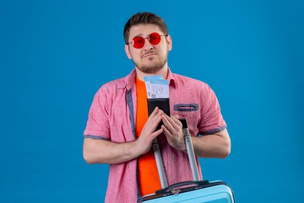Jonge knappe reizigersmens die zonnebril draagt die vliegtuigtickets en koffer houdt