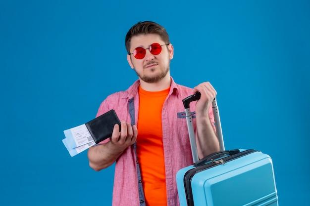 Jonge knappe reizigersmens die zonnebril draagt die vliegtuigtickets en koffer met droevige uitdrukking op gezicht houdt die zich over blauwe muur bevinden