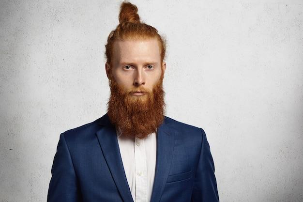Jonge knappe roodharige hipster man met trendy jasje kijkt serieus en peinzend