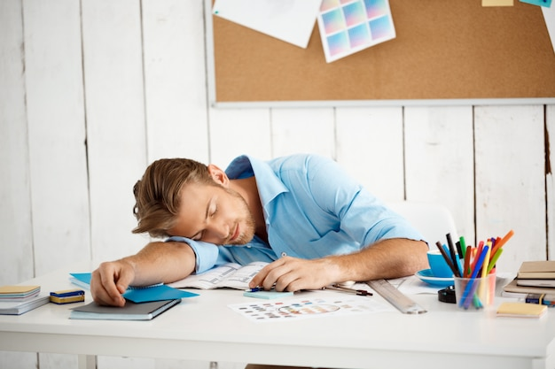 Jonge knappe slaperig moe zakenman slapen aan tafel op papier en kladblok. witte moderne kantoor interieur