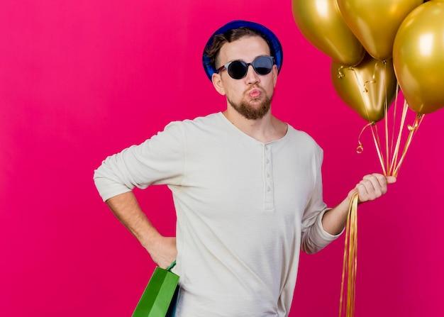 Jonge knappe slavische feestmens met feestmuts en zonnebril met ballonnen en papieren zakken houden hand op taille kijken voorkant doen kus gebaar geïsoleerd op roze muur