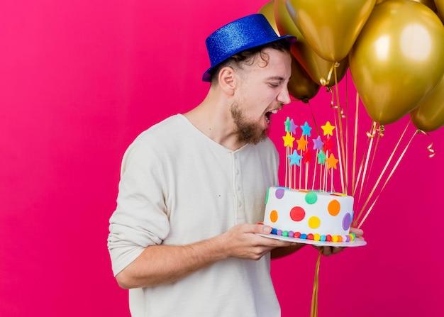 Jonge knappe slavische feestmens met feestmuts met ballonnen en verjaardagstaart met sterren klaar om taart te bijten geïsoleerd op roze muur met kopie ruimte