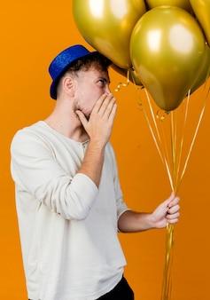 Jonge knappe slavische partijkerel die partijhoed draagt die ballons houdt die recht fluisteren geïsoleerd op oranje muur kijken