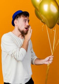 Jonge knappe slavische partijkerel die partijhoed draagt die ballons houdt die voorzijde fluisteren bekijkt die op oranje muur wordt geïsoleerd