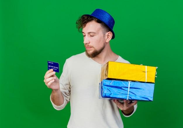Jonge knappe slavische partijkerel die partijhoed draagt die giftdozen en creditcard met gesloten ogen houdt die op groene achtergrond met exemplaarruimte worden geïsoleerd