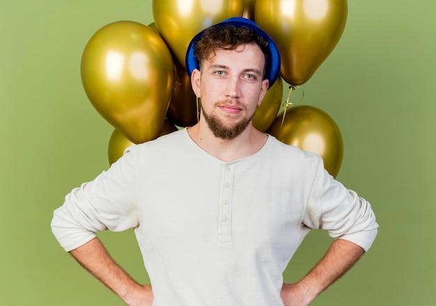 Jonge knappe slavische partijkerel die partijhoed draagt die zich voor ballons bevindt die voorzijde houden die handen op taille houden die op olijfgroene muur wordt geïsoleerd