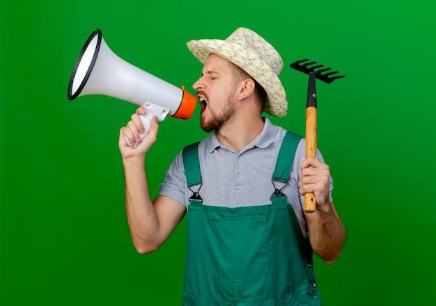Jonge knappe slavische tuinman in uniform en hoed draaien hoofd naar kant houden hark en praten door spreker met gesloten ogen