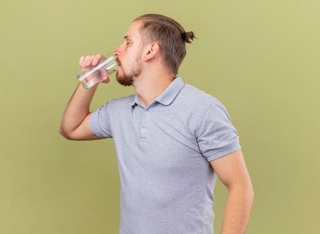 Jonge knappe slavische zieke man drinkwater uit glas met gesloten ogen geïsoleerd op olijfgroene achtergrond met kopie ruimte