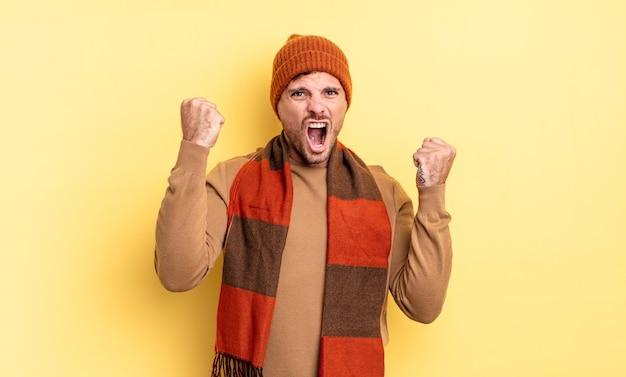 Jonge knappe spaanse man die agressief schreeuwt met een boze uitdrukking of met gebalde vuisten om succes te vieren
