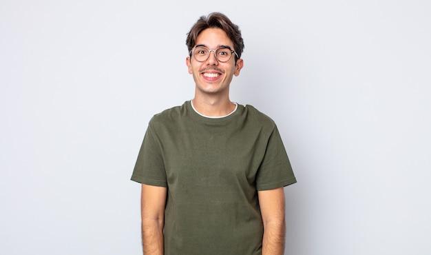 Jonge knappe spaanse man die er gelukkig en gek uitziet met een brede, leuke, gekke glimlach en ogen wijd open