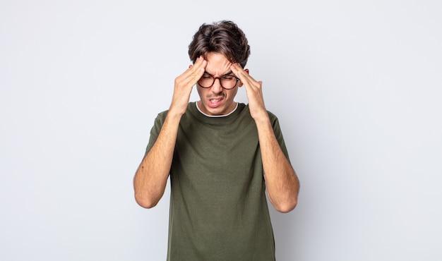 Jonge knappe spaanse man die er gestrest en gefrustreerd uitziet, onder druk werkt met hoofdpijn en last heeft van problemen