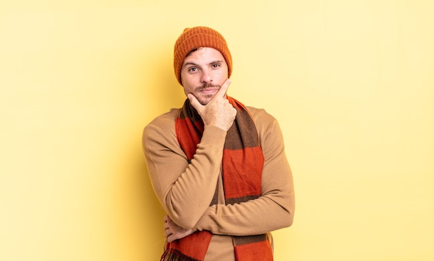 Jonge knappe spaanse man die er serieus, attent en wantrouwend uitziet, met één arm gekruist en hand op de kin, weegopties