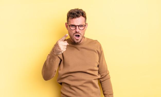 Jonge knappe spaanse man die naar de camera wijst met een boze agressieve uitdrukking die eruitziet als een woedende, gekke baas