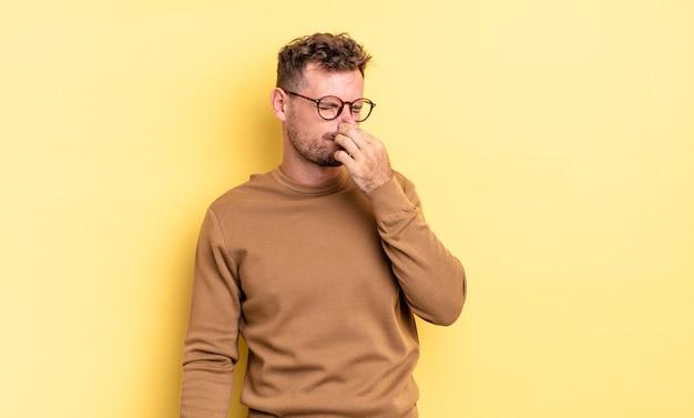 Jonge knappe spaanse man die walgt, zijn neus vasthoudt om te voorkomen dat hij een vieze en onaangename stank ruikt