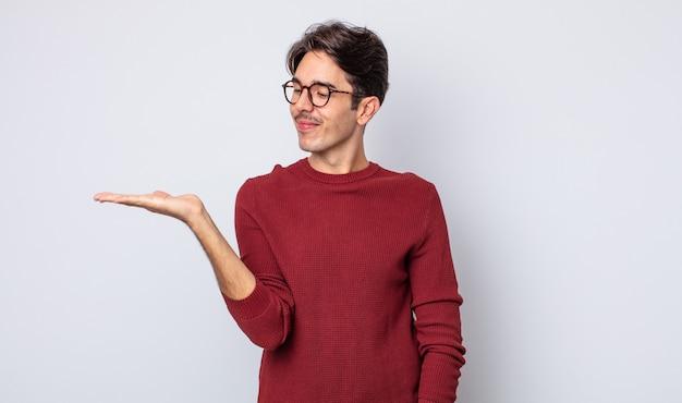 Jonge knappe spaanse man die zich gelukkig voelt en nonchalant glimlacht, kijkend naar een object of concept dat aan de zijkant wordt vastgehouden