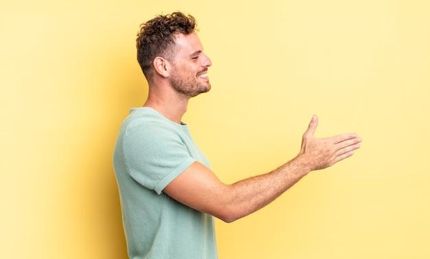 Jonge knappe spaanse man lacht, groet je en biedt een handdruk om een succesvolle deal te sluiten, samenwerkingsconcept