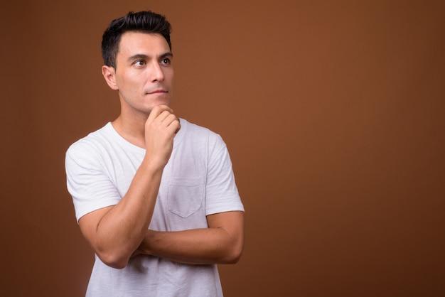 Jonge knappe spaanse man op bruine muur