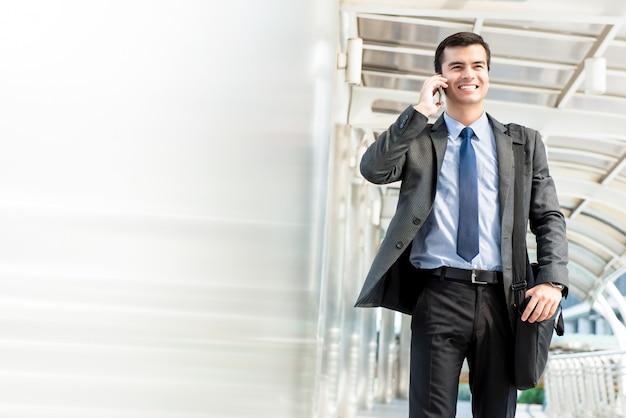 Jonge knappe spaanse zakenman die en op mobiele telefoon loopt uitnodigt