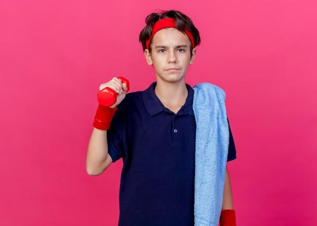 Jonge knappe sportieve jongen die hoofdband en polsbandjes met beugels en handdoek op schouder draagt ?? die aan de voorzijde houdt die halter houdt die op roze muur met exemplaarruimte wordt geïsoleerd
