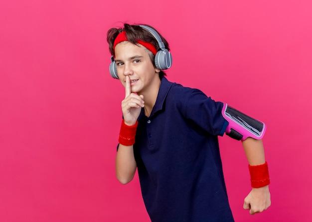 Jonge knappe sportieve jongen met hoofdband en polsbandjes en koptelefoon telefoon armband met beugels kijken camera uitgevoerd gebaren stilte geïsoleerd op karmozijnrode achtergrond met kopie ruimte