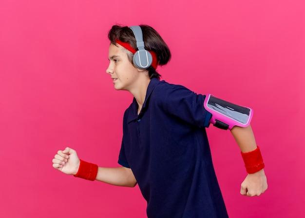 Jonge knappe sportieve jongen met hoofdband en polsbandjes en koptelefoon telefoon armband met beugels uitgevoerd op zoek recht houden handen in de lucht geïsoleerd op karmozijnrode achtergrond