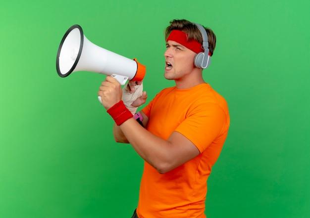 Jonge knappe sportieve man met hoofdband en polsbandjes en koptelefoon en telefoonarmband met gewonde pols omwikkeld met verband in profielweergave pratend door spreker