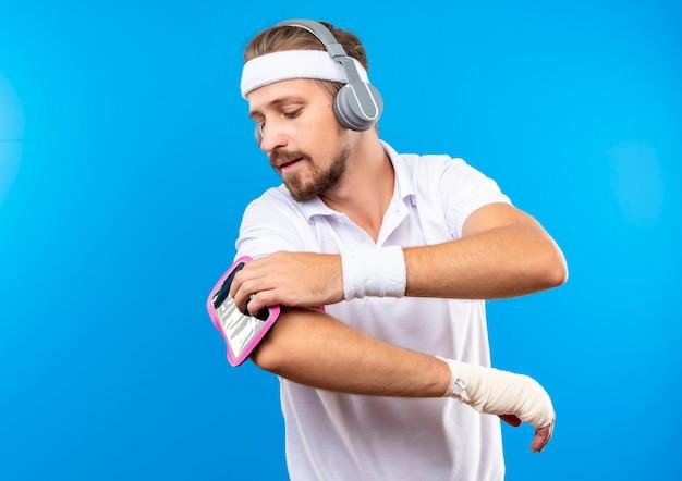 Jonge knappe sportieve man met hoofdband en polsbandjes en koptelefoon met telefoon armband