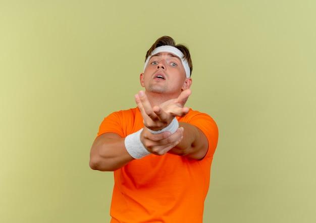Jonge knappe sportieve man met hoofdband en polsbandjes hand strekken op camera en pols houden geïsoleerd op olijfgroene achtergrond met kopie ruimte