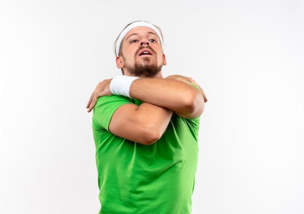 Jonge knappe sportieve man met hoofdband en polsbandjes handen op schouders geïsoleerd op witte ruimte