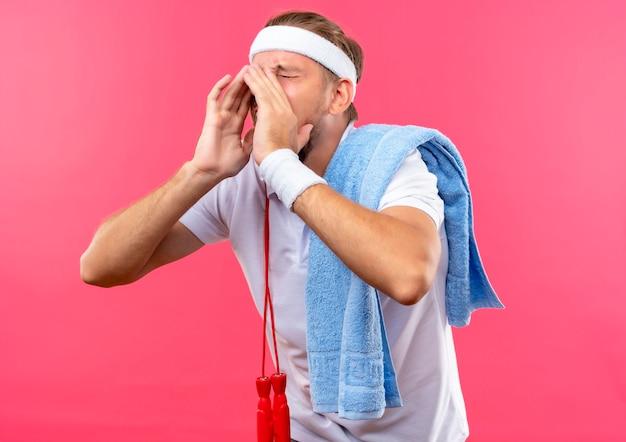Jonge knappe sportieve man met hoofdband en polsbandjes met hardop schreeuwen tegen iemand met handen rond de mond en gesloten ogen met springtouw en handdoek op schouders geïsoleerd op roze ruimte
