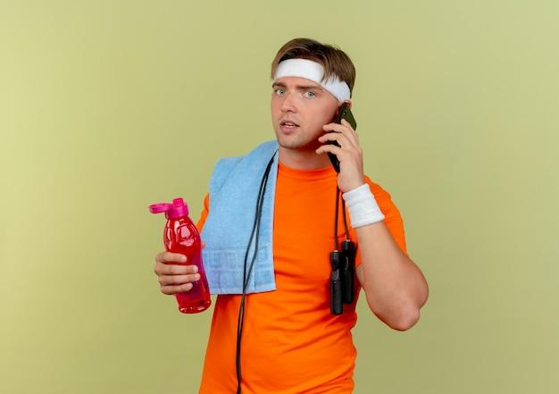 Jonge knappe sportieve man met hoofdband en polsbandjes met springtouw rond de nek en handdoek op schouder waterfles houden en praten over telefoon geïsoleerd op olijfgroene achtergrond met kopie ruimte
