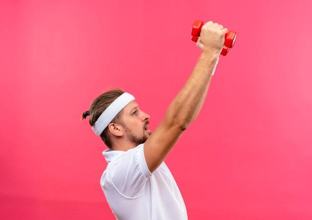 Jonge knappe sportieve man met hoofdband en polsbandjes staande in profiel bekijken verhogen en kijken naar halters geïsoleerd op roze ruimte