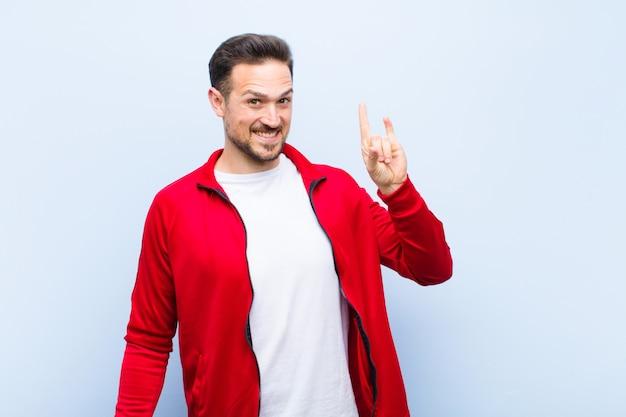 Jonge knappe sportman of -monitor voelt zich gelukkig, leuk, zelfverzekerd, positief en opstandig, maakt rock- of heavy metal-bord met hand tegen platte muur