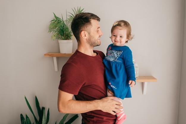 Jonge knappe sterke vader in het houden van haar schattige dochtertje in zijn handen thuis.