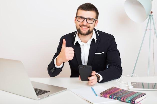 Jonge knappe stijlvolle hipster man in jonge jas aan kantoor tafel
