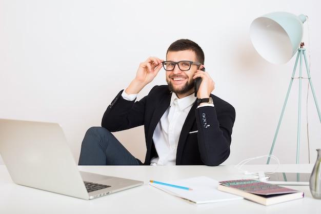 Jonge knappe stijlvolle hipster man in jonge jas zittend aan kantoor tafel