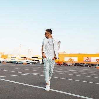 Jonge knappe stijlvolle hipster man in trendy zonnebril in spijkerbroek in een trendy wit t-shirt in sneakers wandelingen in de stad.