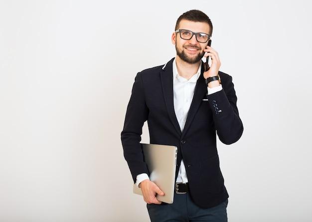 Jonge knappe stijlvolle hipster man in zwarte jas, zakelijke stijl, wit overhemd, geïsoleerd, witte achtergrond, glimlachen, aantrekkelijk, op zoek zelfverzekerd, met laptop, praten over smartphone