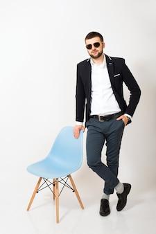 Jonge knappe stijlvolle hipster man in zwarte jas, zakelijke stijl, wit overhemd, geïsoleerd, witte achtergrond, glimlachen, aantrekkelijk, volledige hoogte, er zelfverzekerd en cool uitzien, poseren met bureaustoel