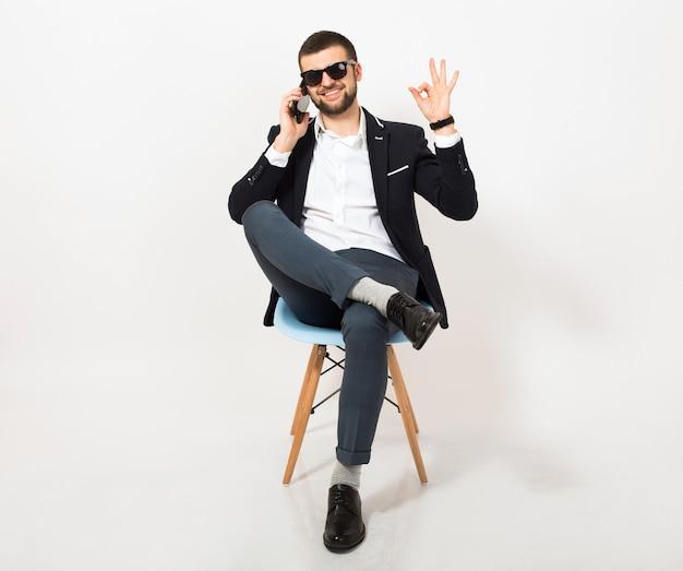 Jonge knappe stijlvolle hipster man in zwarte jas, zakelijke stijl, wit overhemd, geïsoleerd, zittend ontspannen op bureaustoel, praten over smartphone, glimlachen, gelukkig, positief, zonnebril