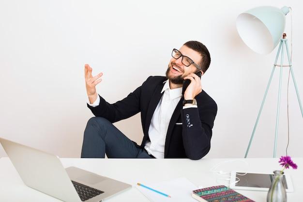 Jonge knappe stijlvolle hipster man in zwarte jas zittend aan de tafel van het kantoor, zakelijke stijl, wit overhemd, geïsoleerd, werken, laptop, opstarten, werkplek, praten over smartphone, glimlachen, positief