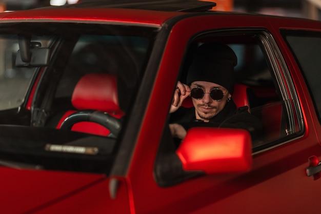 Jonge knappe stijlvolle man chauffeur met zonnebril in een zwarte jas met een hoed zit achter het stuur en rijdt in een vintage rode auto
