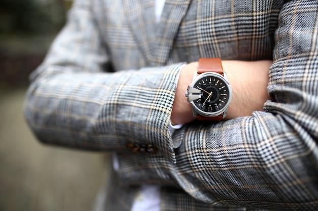 Jonge knappe stijlvolle man gekleed in moderne formele kleding dichtknopen jas. sluit omhoog van handen van kerel in grijs jasje, violet overhemd. persoon klaar voor huwelijksviering of afstuderen.