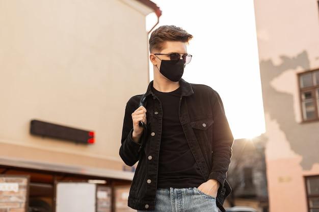Jonge knappe stijlvolle man model in stijlvol zwart spijkerjack met rugzak in vintage zonnebril in zwart trendy beschermend masker