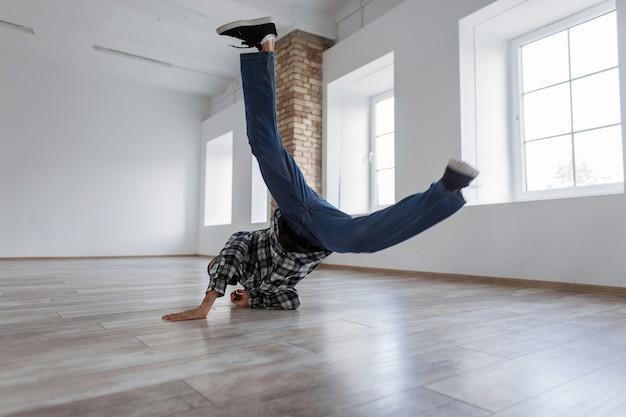 Jonge knappe stijlvolle mannelijke danser in vrijetijdskleding dansen in beweging op de dansstudio