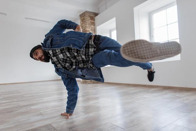 Jonge knappe stijlvolle mannelijke danser met een pet in modieuze denim kleding breakdance dansen in een dansstudio