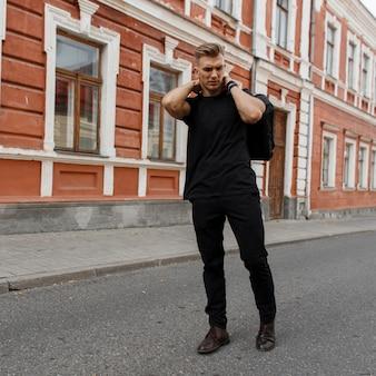 Jonge knappe stijlvolle model man in zwarte mockup t-shirt en broek met zwarte tas op straat in de stad