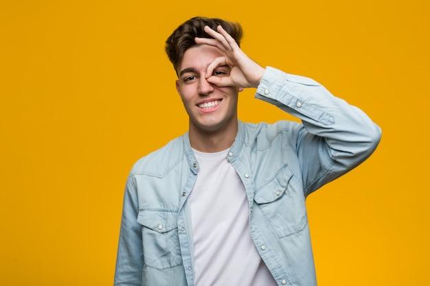 Jonge knappe student die een denimoverhemd draagt opgewekt het houden van ok gebaar op oog.